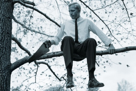 man-sitting-on-branch-while-sawing-it-of_450