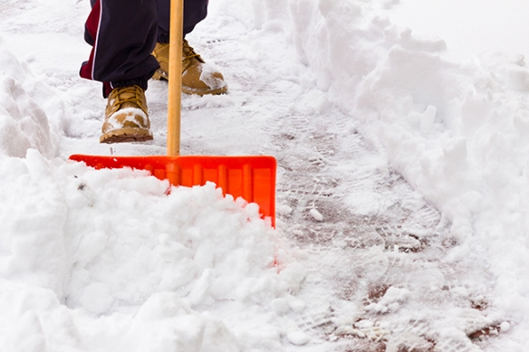 Close-up of shovel as man clears snow  from path